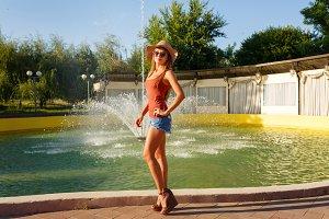 Trendy girl standing near fountain