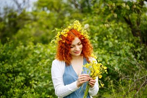 Girl weaves a wreath of wildflowers.