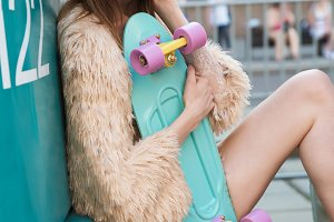 Beautiful and fashion young woman posing with a skateboard on city street