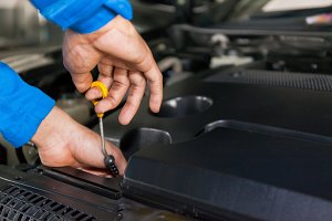 Mechanic checking car's oil level in a car service garage