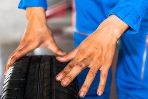 Mechanic holding and checking car wheel in car garage service