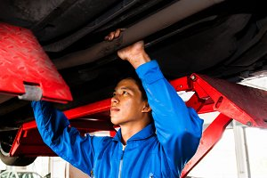 Mechanic standing and fixing under a lifted car with copy space