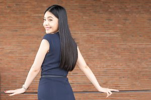 Confident Asian business woman turning around with red brick wall interior