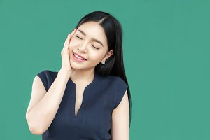 Beautiful young Asian woman face isolated on green background