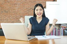 Excited Asian woman raising her arms while working on her laptop - success and business concept
