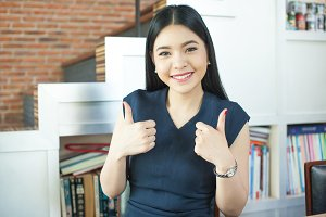 Asian woman giving double thumbs up in modern office