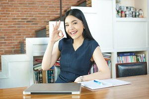 Asian Young Woman sitting with laptop computer and ok sign