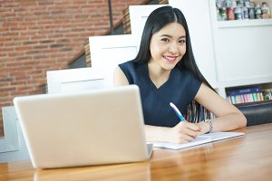 Beautiful Asian woman smiling and writing a notebook on table with laptop aside