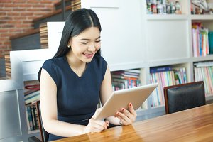 Beautiful Asian woman playing with her tablet