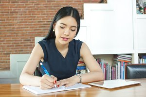 Beautiful Asian woman writing a notebook on table in modern interior