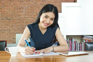 Beautiful Asian woman smiling and writing a notebook on table