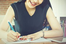 Beautiful woman smiling and writing a notebook on table (Focus on Mouth)
