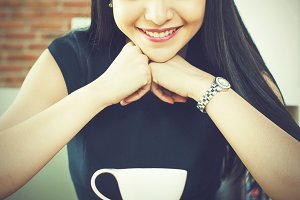 Asian woman looking at coffee cup and loving it in modern cafe