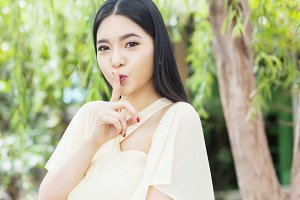 Beautiful Asian woman with her top secret gesture