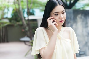 Unhappy Asian woman on phone - relationship and family concept