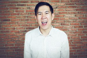 Angry Asian business man in red brick wall background