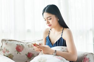 Asian woman playing her phone on a cozy sofa
