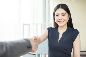 Smart and confident Asian businesswoman smiling and shaking hands