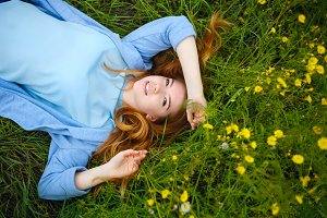 Girl lies on meadow