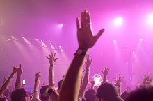Music band crowds raising hands up in the air (Selective focus)