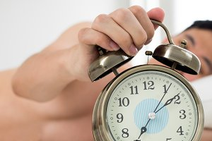 Alarm clock with man waking up on bed in background (Shallow depth of field)