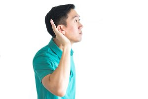 Young asian man trying to listen to something