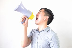 Young Asian man shouting with a megaphone isolated white background