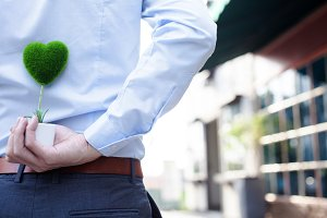 Man hands holding surprise gift from behind - love and relationship concept