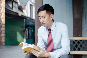 Asian Man Reading a Book Sitting on Bench