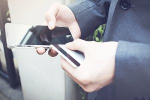 Businessman holding a credit card and using smartphone to make mobile payment. (selective focus on phone)