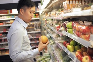 Young Asian man selecting a fruit from supermarket