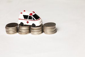 Ambulance on coins pile with copy space - Insurance, Healthcare and Medical cost concept