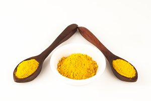turmeric in two wooden spoons