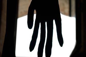 Black hand in front of the window