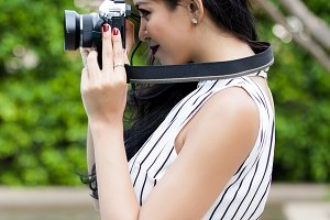 Young woman photographer taking photo over green tourist attraction background