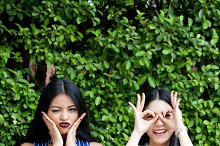 Two happy female best friends having fun with crazy and playful expressions on green bush background