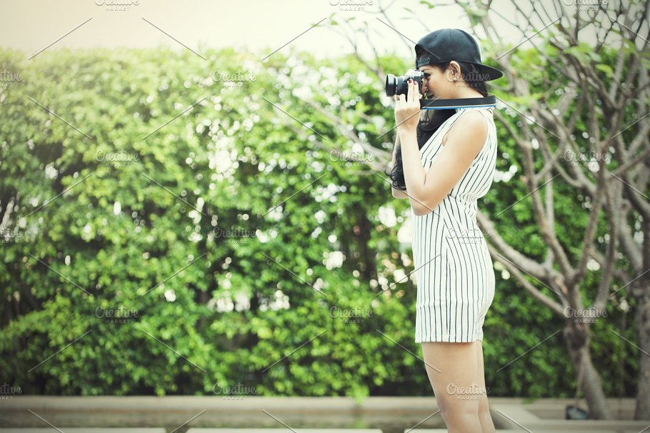 woman photographer taking a photo in outdoor nature scene vintage