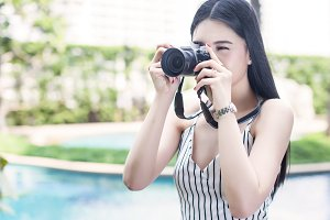 Fashionable and vintage woman taking a photo with vintage camera