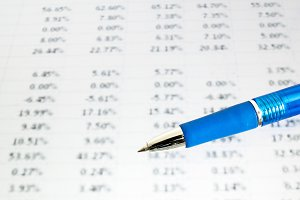 Blue pen on financial data (focus on pen, blurred out the data)