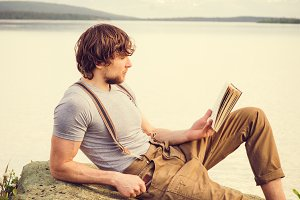 Young Man reading book outdoor
