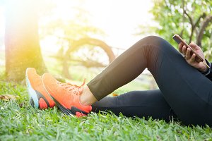 Young woman in fitness clothes is relaxing in outdoor park