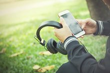Young woman using apps on smartphone to play music in park
