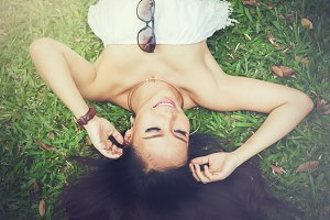 Young happy and smiling woman laying down on green grass