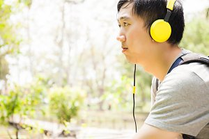 Young man listening to music with headphone and carrying a bag in green outdoor park with copy space