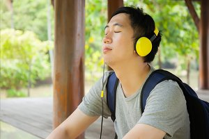 Young man listening to music with headphone and carrying a bag in green outdoor park