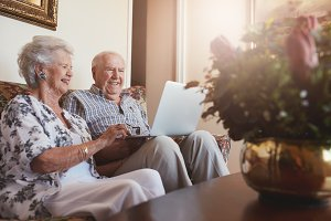 Smiling senior couple using laptop
