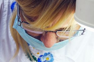 Close up portrait of female doctor in glasses with protective work wear. Female face in medical mask. Cosmetologist or therapist is working