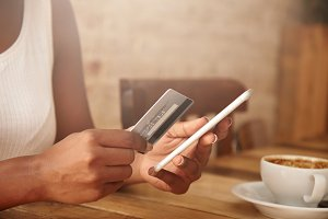 Selective focus. Close up shot of female hands holding plastic card and cell phone. African woman paying with credit card while shopping online, using mobile phone, having cappuccino at a restaurant