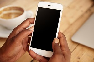 Close up of black woman's hands holding smart phone with blank copy space for your advertising content or promotional information. Female downloading updates on her mobile phone, sitting at a cafe