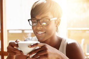 People, drinks and leisure concept: happy dark-skinned woman wearing glasses, drinking tea from cup or mug at home. Beautiful young African female enjoying a cup of cappuccino while relaxing indoors